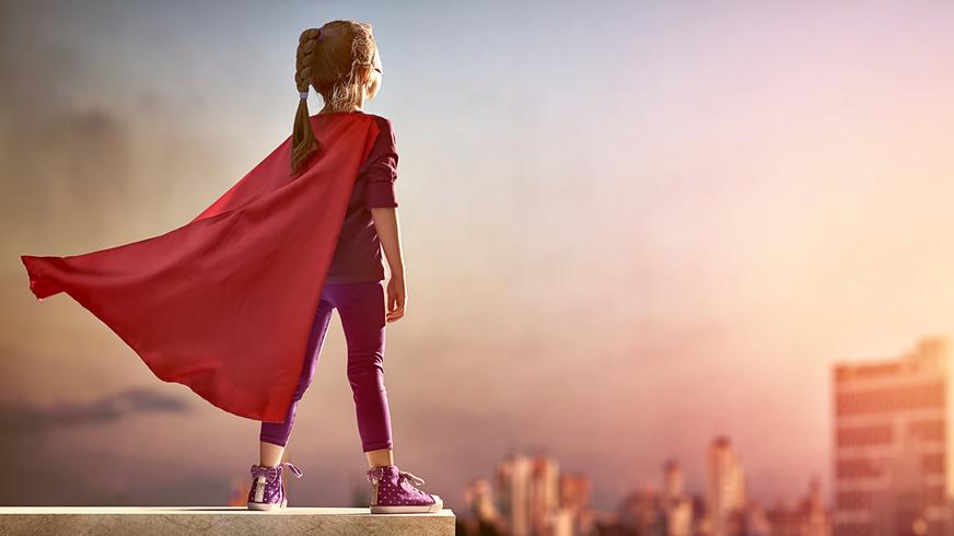 Kleines Mädchen spielt Superheldin.